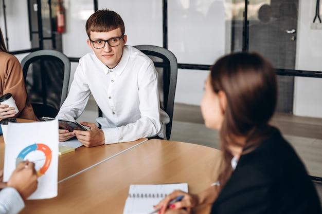 Jonge man in glazen op zakelijke bijeenkomst, aandachtig luisteren naar zijn collega