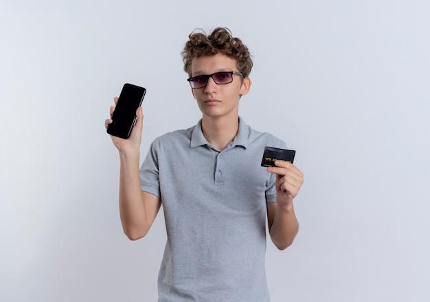 Jonge man in grijs poloshirt die de creditcard van de smartphoneholding met ernstig gezicht toont die zich over witte muur bevinden