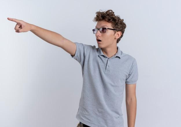 Jonge man in grijs poloshirt op zoek verrast wijzend met wijsvinger naar iets staande over witte muur