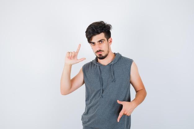 Jonge man in grijs shirt die geweergebaren laat zien en er serieus uitziet?