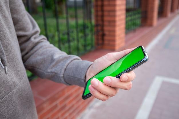 Jonge man in grijs sweatshirt houdt een telefoon met groen scherm buiten