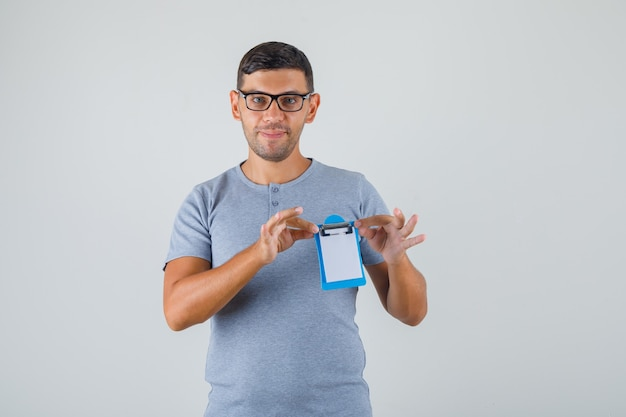 Jonge man in grijs t-shirt, bril met mini klembord en op zoek blij