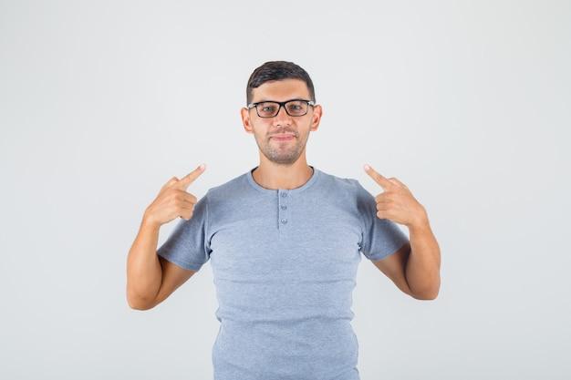 Jonge man in grijs t-shirt, bril wijzende vingers naar zichzelf en lachend