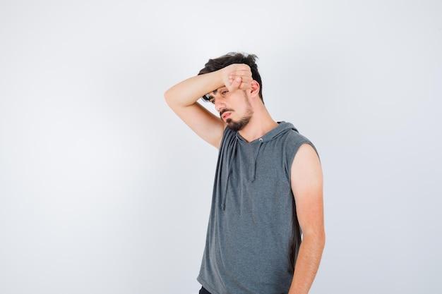 Jonge man in grijs t-shirt die arm op het voorhoofd zet en er serieus uitziet?