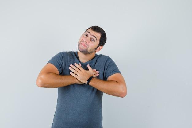Jonge man in grijs t-shirt hand in hand op de borst en op zoek dankbaar