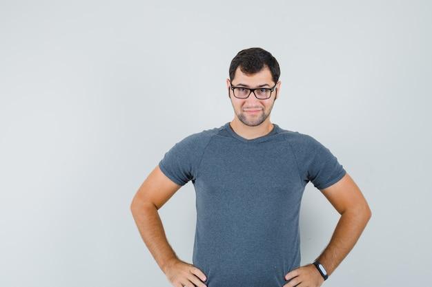 Jonge man in grijs t-shirt hand in hand op de taille en op zoek intelligent