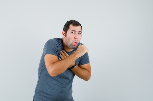 Jonge man in grijs t-shirt hoest lijden en ziek kijken