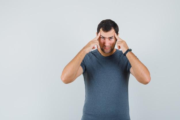 Jonge man in grijs t-shirt lijdt aan sterke hoofdpijn en ziet er uitgeput uit