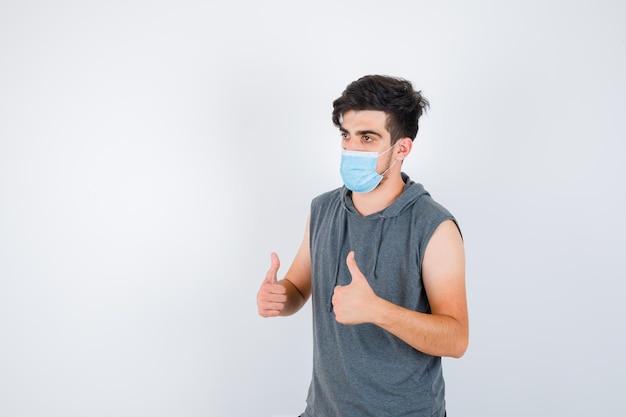 Jonge man in grijs t-shirt met masker terwijl hij zijn duimen laat zien en er serieus uitziet
