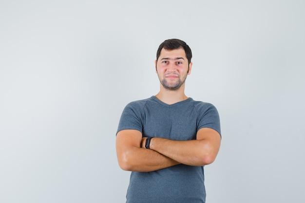 Jonge man in grijs t-shirt staan met gekruiste armen en op zoek zelfverzekerd