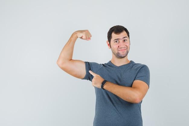 Jonge man in grijs t-shirt wijzend op de spieren van de arm en kijkt zelfverzekerd