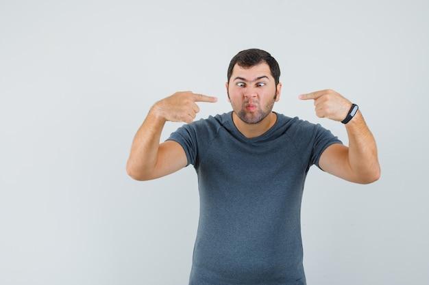 Jonge man in grijs t-shirt wijzend op zijn neus en ziet er grappig uit