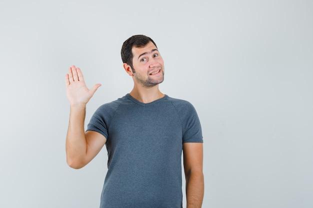 Jonge man in grijs t-shirt zwaaiende hand voor groet en op zoek vrolijk
