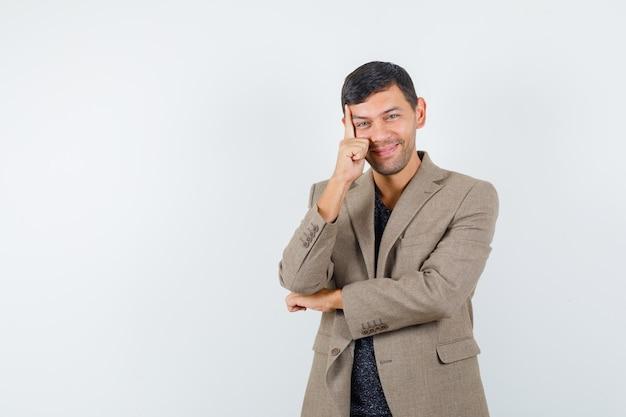 Jonge man in grijsachtig bruin jasje poseren en ziet er indrukwekkend uit, vooraanzicht.