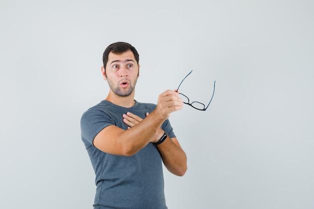Jonge man in grijze t-shirt bril te houden en op zoek verward