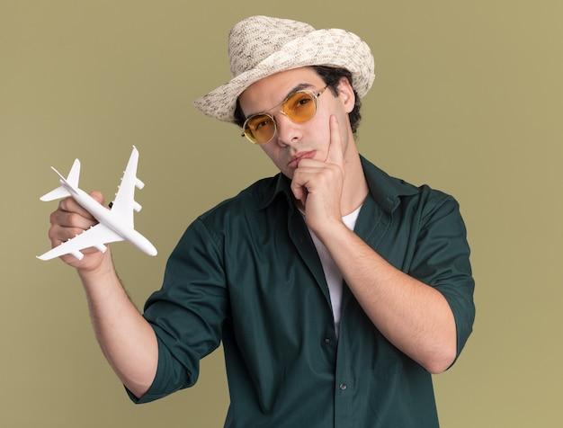 Jonge man in groen overhemd en zomerhoed die een bril draagt die stuk speelgoed vliegtuig houdt die voorzijde met peinzende uitdrukking bekijkt die zich over groene muur bevindt
