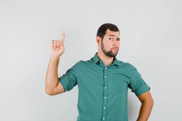 Jonge man in groen shirt die met vragende manier omhoog wijst en er gefocust uitziet, vooraanzicht.