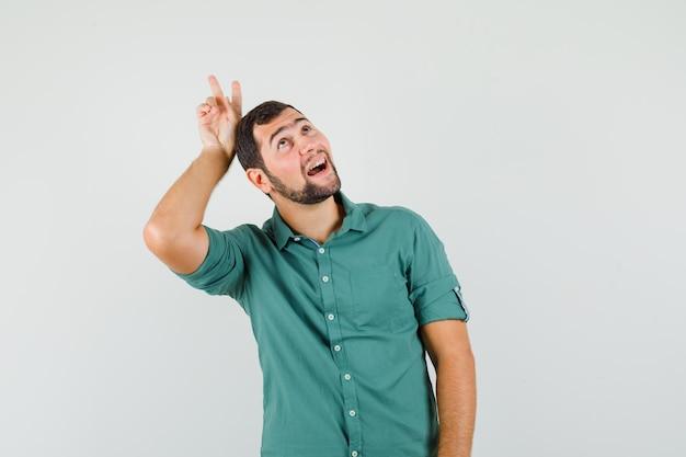 Jonge man in groen shirt die v-teken op zijn hoofd maakt en er grappig uitziet, vooraanzicht.