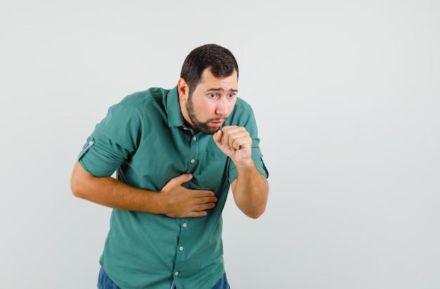 Jonge man in groen shirt hoest en ziet er ongemakkelijk uit, vooraanzicht.