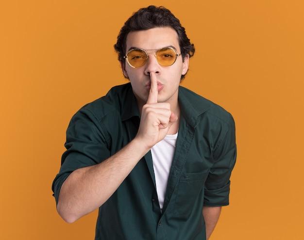 Jonge man in groen shirt met bril kijken voorkant stilte gebaar maken met vinger op lippen staande over oranje muur