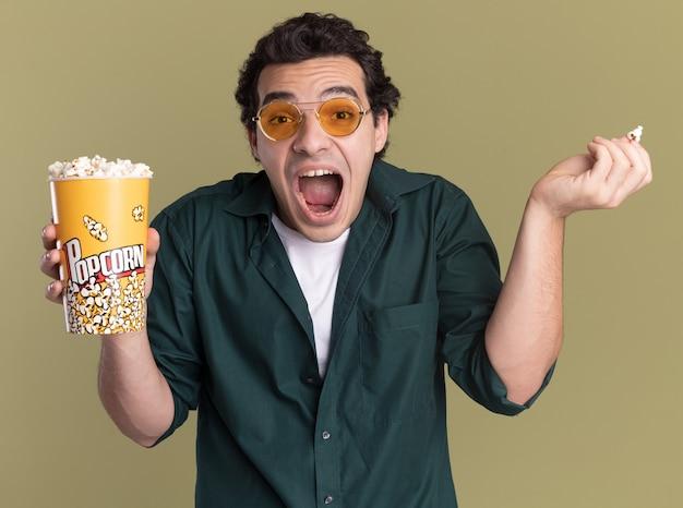 Jonge man in groen shirt met bril met emmer met popcorn kijken naar voorkant schreeuwen opgewonden en emotioneel staande over groene muur