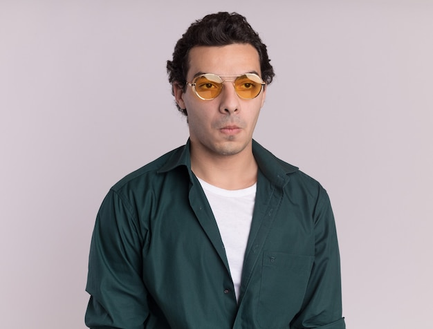 Jonge man in groen shirt met bril op zoek opzij verward staande over witte muur