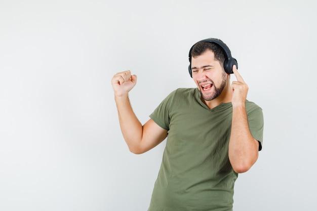 Jonge man in groen t-shirt genieten van muziek met winnaargebaar en op zoek vrolijk