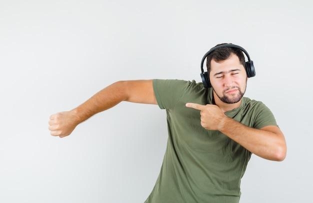 Jonge man in groen t-shirt wijst naar kant terwijl u geniet van muziek en er speels uitziet