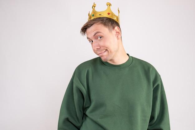 Jonge man in groene trui met kroon op zijn hoofd op wit