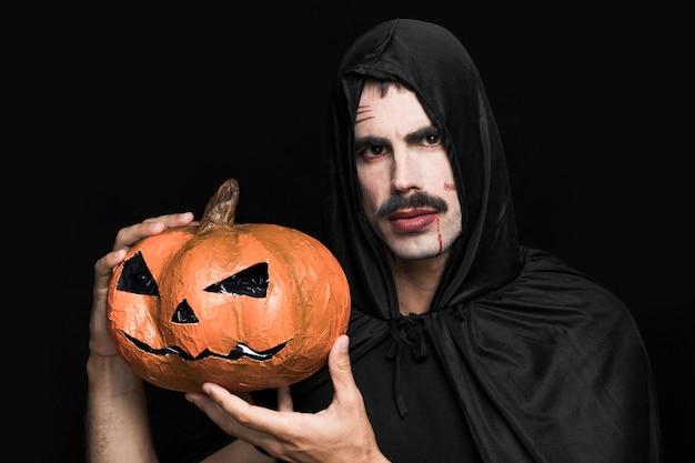 Jonge man in halloween-kostuum die decoratieve pompoen houden