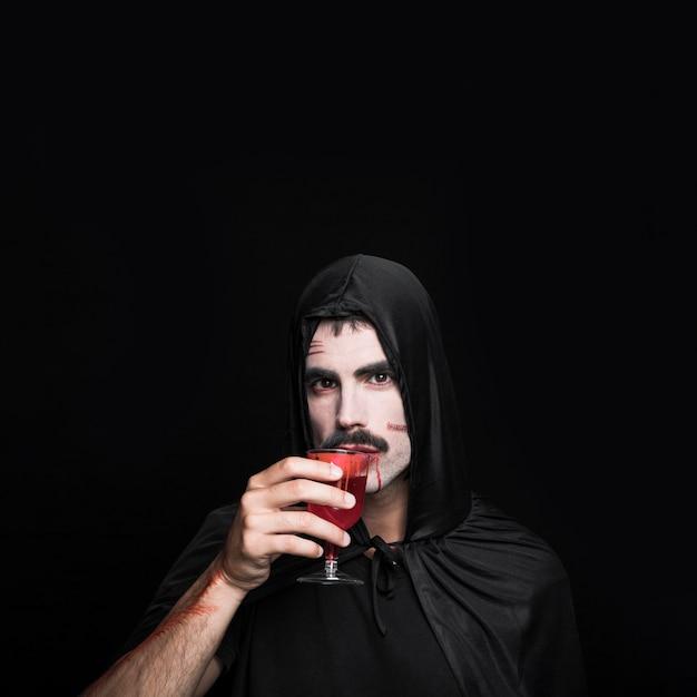 Jonge man in halloween-kostuum die rode vloeistof in studio drinken