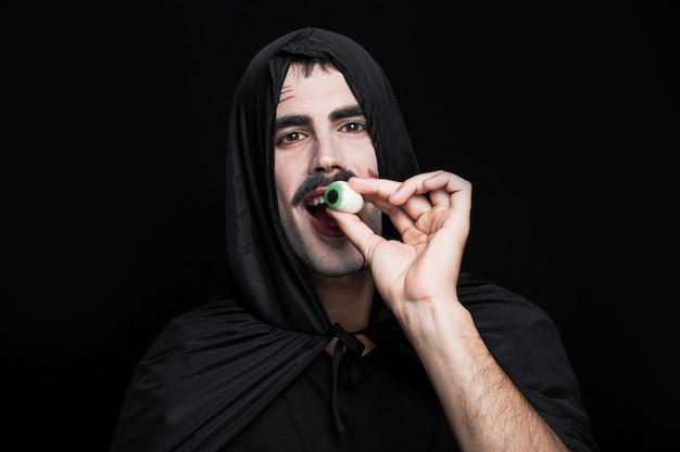 Jonge man in halloween-kostuum stellen in studio met kunstoog