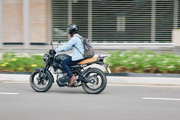 Jonge man in helm met rugzak snel rijden op motorfiets langs stadswegen