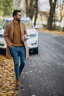 Jonge man in het bos dragen jas door de auto
