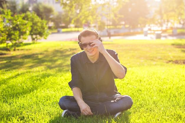 Jonge man in het park luisteren naar de muziek.