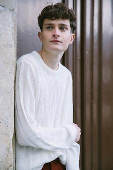 Jonge man in het wit zijwaarts op zoek