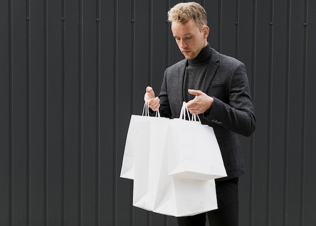 Jonge man in het zwart in boodschappentassen kijken