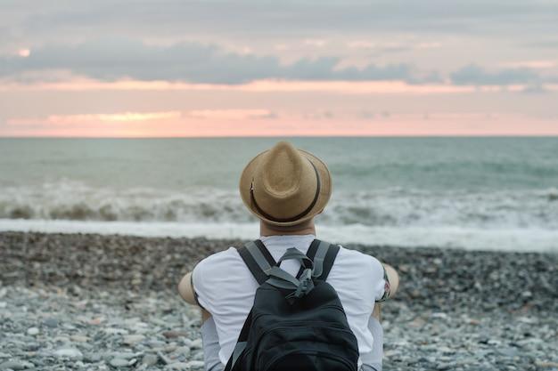 Jonge man in hoed en met rugzak zittend op het strand