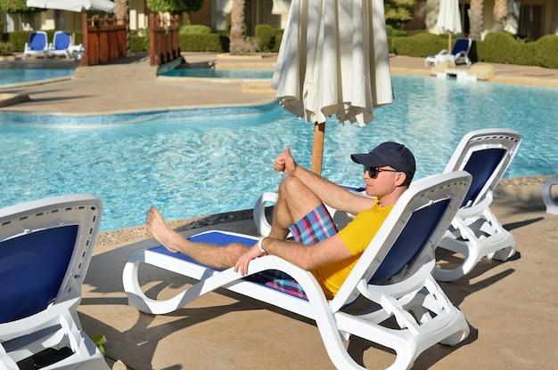 Jonge man in hoed en zwarte zonnebril liggend op een ligstoel in het hotel in de buurt van zwembad.