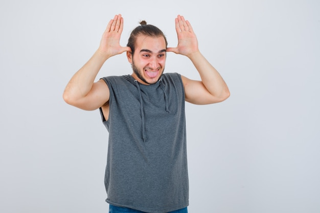 Jonge man in hoodie grimas maken en op zoek vrolijk, vooraanzicht.
