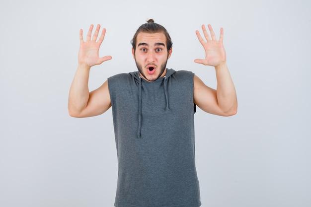 Jonge man in hoodie met overgave gebaar en op zoek verrast, vooraanzicht.