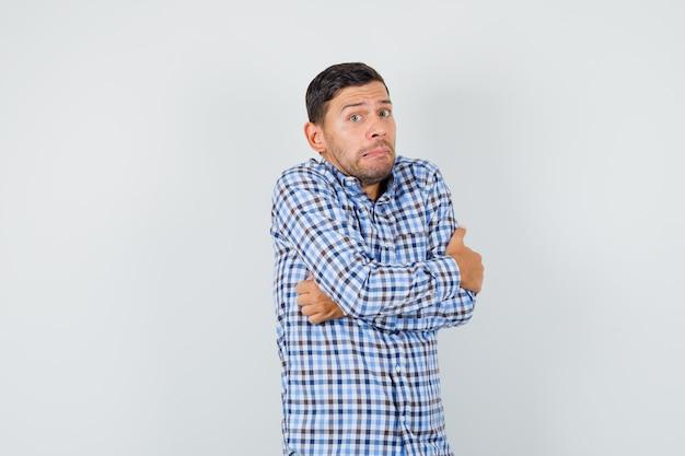 Jonge man in ingecheckte overhemd knuffelen zichzelf en op zoek nederig
