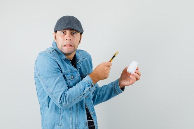 Jonge man in jas, glb op zoek fles pillen met vergrootglas en op zoek verontrust