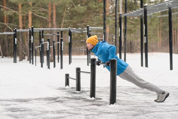 Jonge man in jas met lage horizontale balk om pull-ups op sportveld in de winter te oefenen
