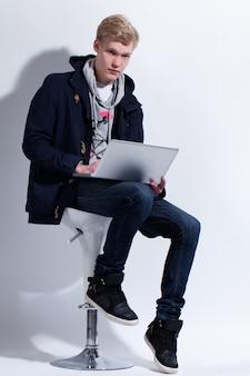 Jonge man in jas met laptop