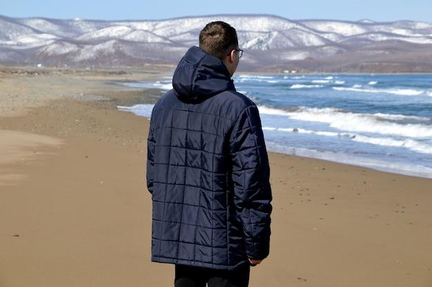 Jonge man in jas wandelen op het strand van de japanse zee
