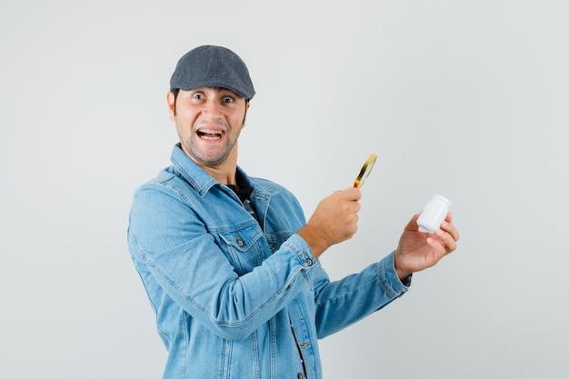 Jonge man in jasje, glb op zoek fles pillen met vergrootglas en op zoek tevreden