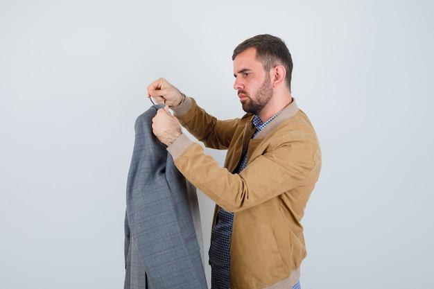 Jonge man in jasje, overhemd kijkt naar pakken, staat zijwaarts en kijkt weemoedig.
