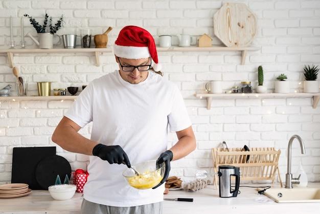 Jonge man in kerstman hoed deeg maken in de keuken