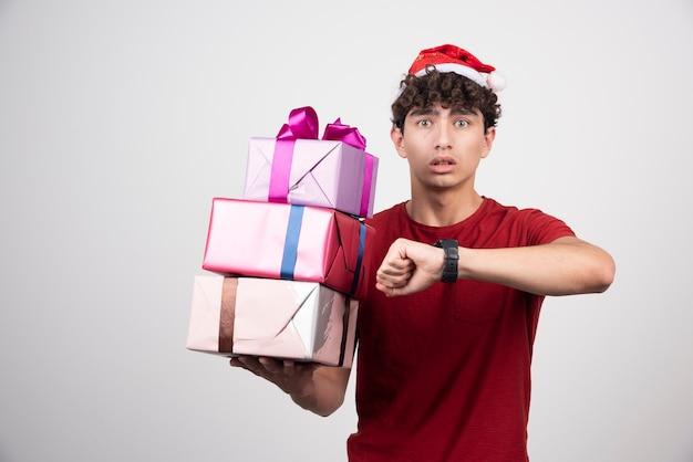 Jonge man in kerstmuts kijken naar de tijd.